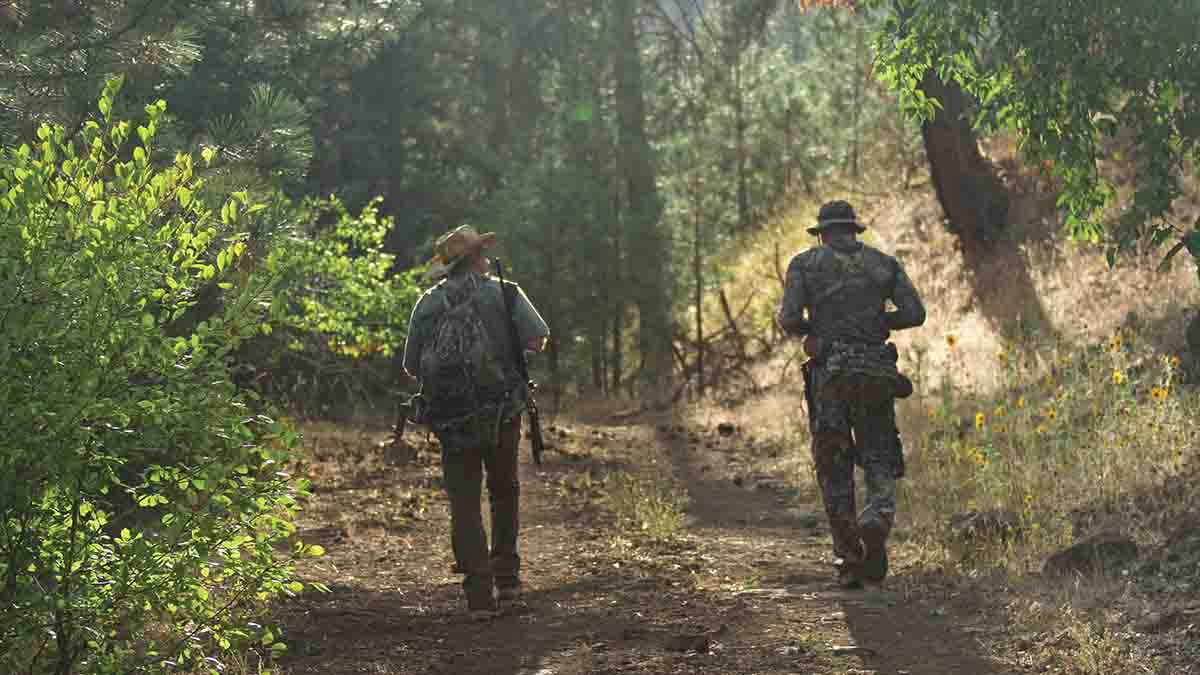 Lucas Simpson (right) and Gary head up a creek bottom to the site of an old homesteader orchard to try to call in a fruit-eating bear with a predator call. Animals came to the call but remained unseen at the edge of the tree line.